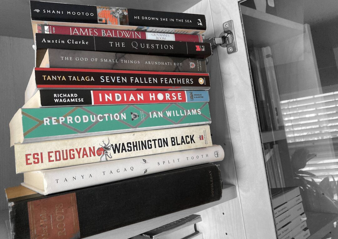Books by BIPOC authors are in vibrant colours on a black-and-white shelf